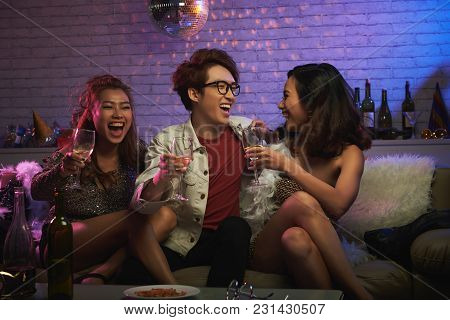 Group Of Young Friends Gathered Together At Night Club, Drinking Champagne And Laughing While Celebr