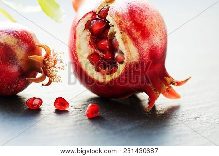 Ripe Red Fruit Pomegranate With Seeds On Black Stone Background. Close-up Photo Shallow Depth Of Fie