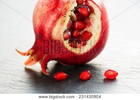 Macro View Ripe Red Fruit Pomegranate With Seeds On Black Stone Background. Shallow Depth Of Field
