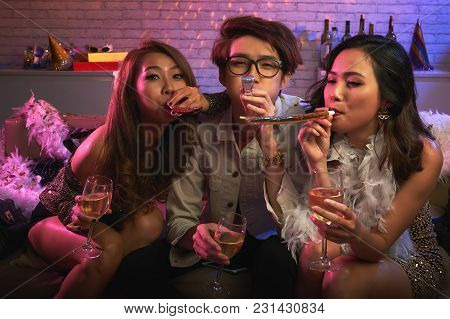 Group Portrait Of Cheerful Asian Friends Sitting On Sofa With Champagne Flutes In Hands, Looking At