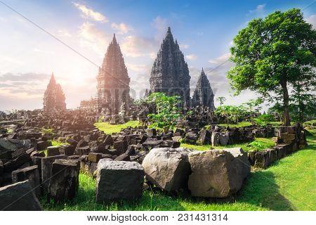 Ancient stone ruins on green field and Candi Prambanan or Rara Jonggrang, Hindu temple compound on background. Impressive architectural site. Yogyakarta, Central Java, Indonesia. Panoramic view.