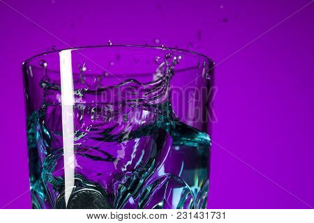 The Water Splashing In Glass On Lilac Background At Studio. Vivid Bright Colored Lighting. Trendy In