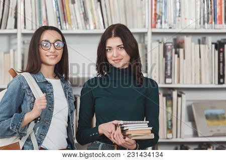 Smiling Multicultural Friends Looking At Camera In Library
