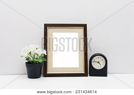 Mockup 8x10 - A Dark Wooden Frame With With Flowers And Balck Watch. Vertical Orientation.