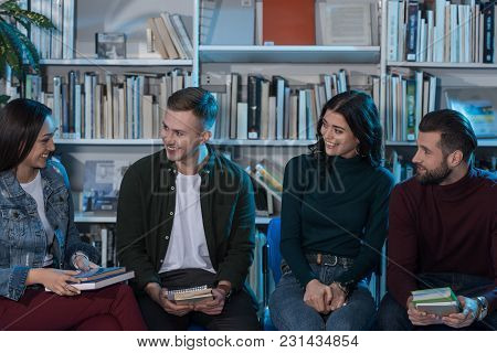 Four Happy Multicultural Friends With Books In Library