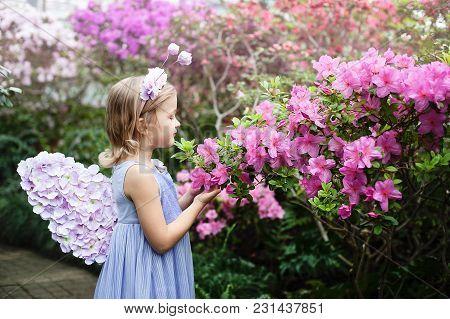 Girl Sniffing Flowers Of Azaleas. Flowering Azaleas In The Park