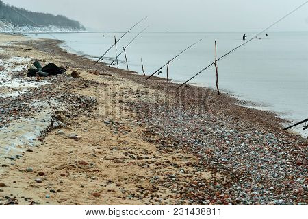 Fishing Rods On The Sea Shore, Winter Fishing At Sea, Fishing Rods Placed On The Shore Of The Pond