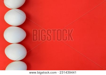 A Few White Eggs On A Bright Red Background