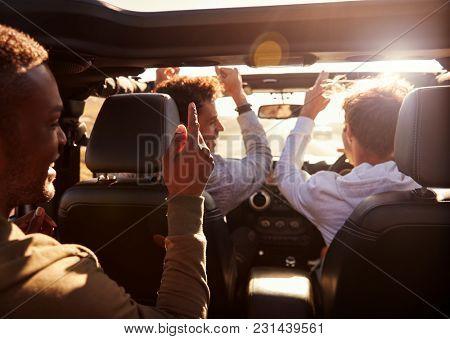 Three young adult men having fun driving an open top car