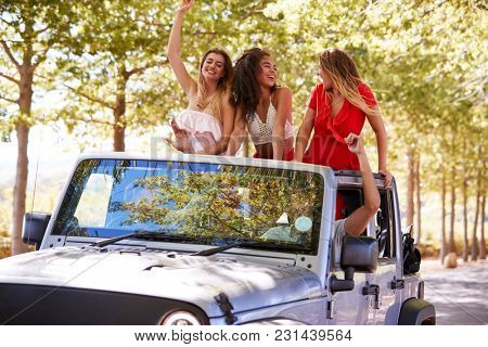 Friends driving on empty road in an open top car, close up
