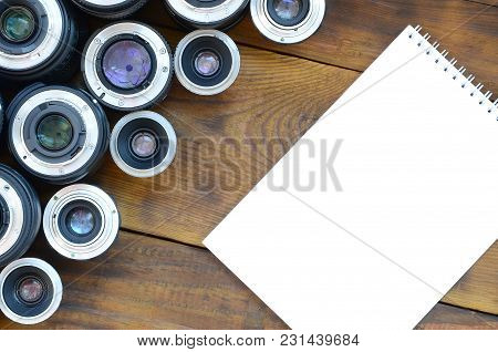 Several Photographic Lenses And White Notebook Lie On A Brown Wooden Background. Space For Text