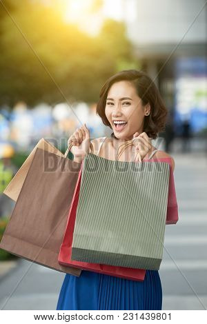 Excited Young Vietnamese Woman With Bags Full Of Purchases