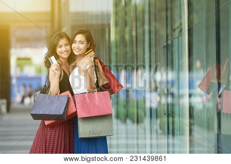 Happy Young Vietnamese Women With Paper-bags Showing Credit Cards