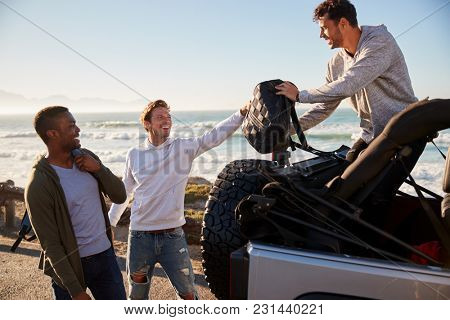 Three young adult male friends unloading backpacks from jeep