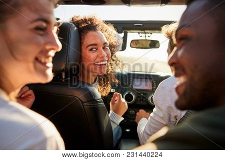 Young woman turning round in front passenger seat of a car