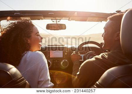 Three young adult friends in a car on a road trip together
