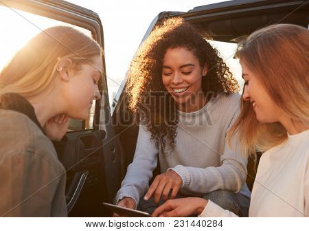 Female friends planning road trip route with tablet computer