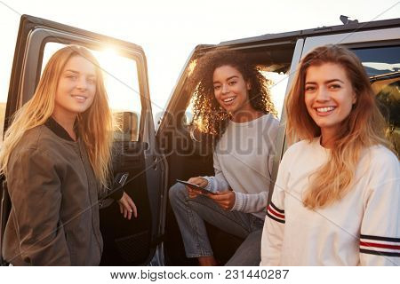 Three female friends on a road trip using a tablet, close up