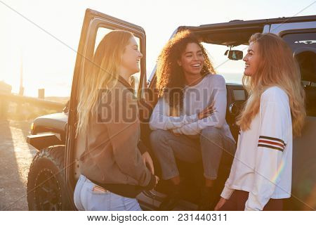 Three young female friends on a road trip talking beside car