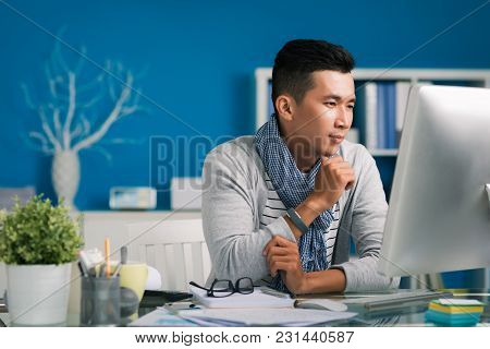 Yuong Asian Designer Reading Information On Computer Screen