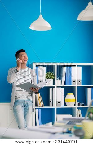 Happy Mixed-race Businessman With Folder Of Documents Calling On Phone