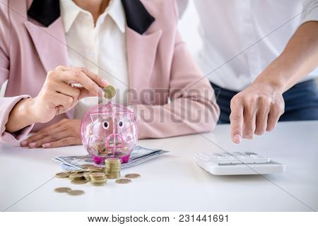 Two Couples Putting Coins Into Piggy Bank, Writing To Report And Using Calculator To Analysis Busine