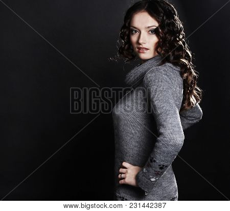 Beautiful Young Woman In Sweater And Boots Poses For The Camera.isolated On Black Background