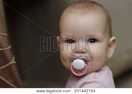 Little Baby Smiles With Pacifier In Pink Dress