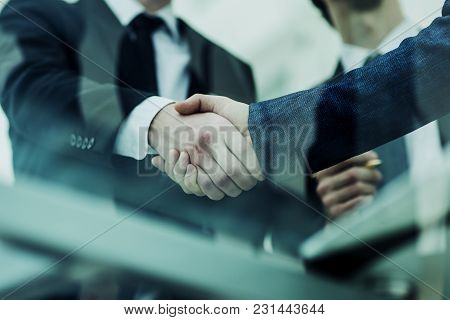 Closeup Of Handshake Of Business Partners On Background Of Office