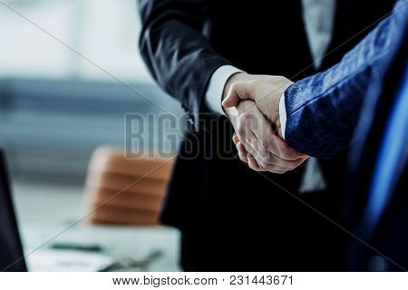 Closeup Of Handshake Of Business Partners On The Background Of Bright Office.