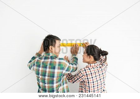 Cheerful Vietnamese Young Couple Redecorating Apartment Together