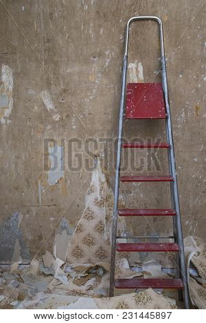 Old Dilapidated Concrete Wall With Removed Wallpaper And A Ladder During A Renovation Of A House
