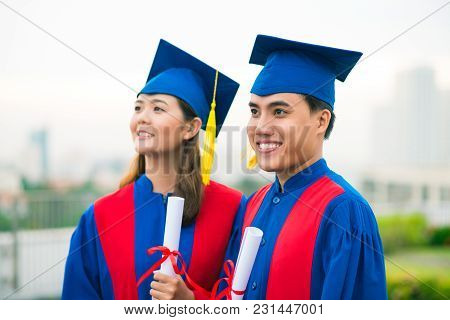 Happy Vietnamese Students In Graduation Gowns Standing Outdoors