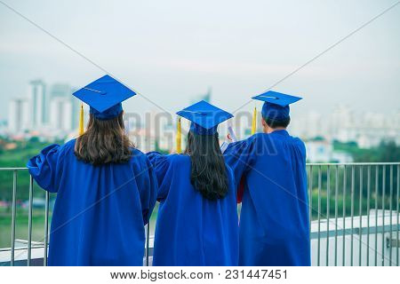 Rear View Of Graduates In Gowns And Hats