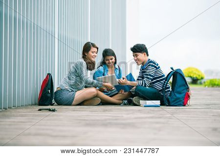 Smling College Student Showing Something Interesting On Tablet Computer To Her Friends