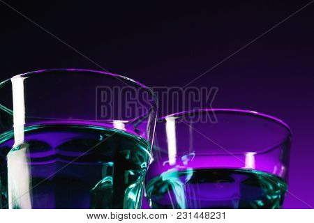 The Water In Two Glasses On Lilac Background At Studio. Vivid Bright Colored Lighting. Trendy In 201