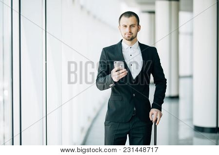 Happy Young Businessman Walking And Looking At Mobile Phone At Airport. Handsome Business Executive