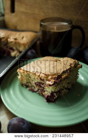 Plum Cake With Coffee On A Wooden Table