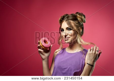 Cheerful young woman in bikini and top stands with tasty donut on a pink background. Pin up style.