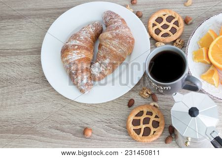 European Breakfast With 2 Big Croissants On White Plate, Coffee Mug And Sliced Juicy Orange With Cak