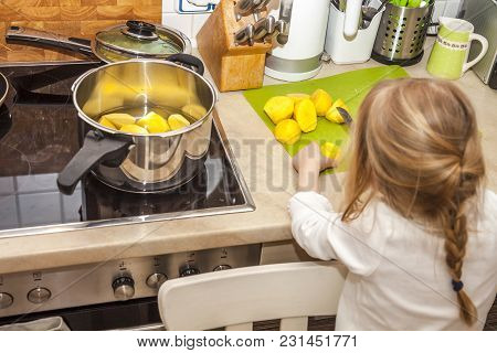The Little Girl Peeling And Cutting Potatoes.