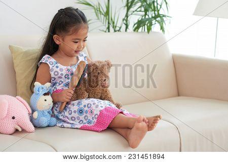 Little Girl Sittin Gon Sofa And Brushing Her Stuffed Bear