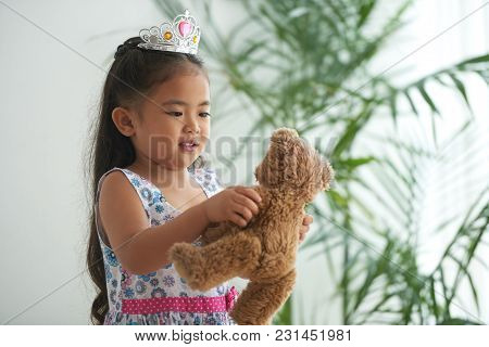 Asian Girl In Plastic Crown Playing With Teddy Bear