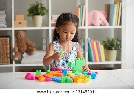 Little Asian Girl Playing With Plastic Cubes