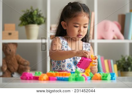 Little Girl Playing With Bright Plastic Blocks