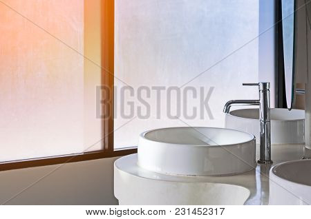 White Ceramic Wash Sink Basin And Faucet With Window In The Restroom