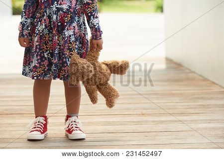 Cropped Image Of Girl Standing Outdoors With Teddy Bear
