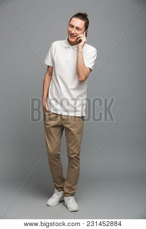 Image of cheerful young man standing isolated over grey wall background. Looking aside talking by cellphone.