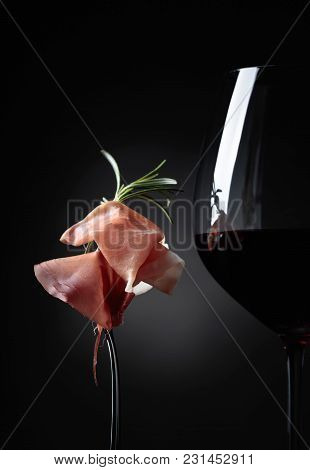 Glass Of Red Wine With Prosciutto And Rosemary On A Black Background.