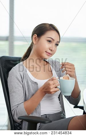 Portrait Of Pensive Female Entrepreneur Drinking Tea At Her Workplace